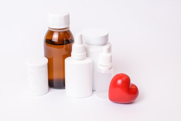 Remédio cura farmacêutico dor rx símbolo psiquiátrico cardíaco farmácia cap tampa parafuso conceito de objeto. perto de caixas com gotas de comprimidos para olhos de orelhas com pequeno coração isolado na superfície branca