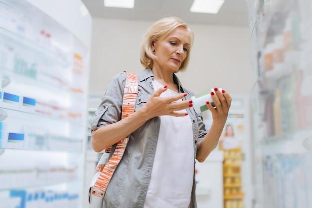 Remédio desconhecido. cliente sênior concentrado em pé entre as prateleiras enquanto vai comprar probióticos