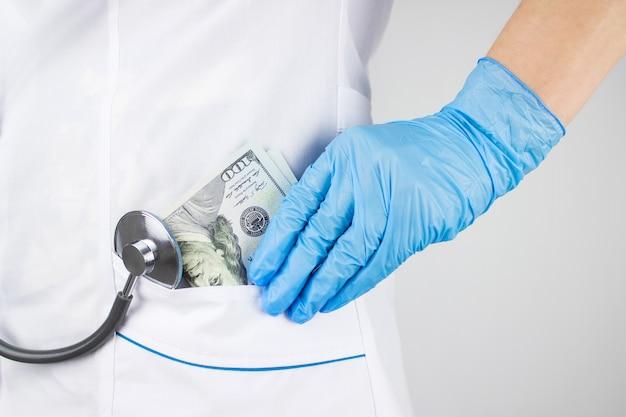 Remédio pago. custos do seguro médico. médico colocando dinheiro no bolso. conceito de corrupção. conceito de pagamento de saúde.