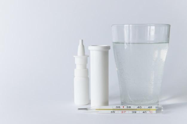 Remédio para pulverização nasal, frasco de comprimidos brancos, termômetro médico de mercúrio e vidro