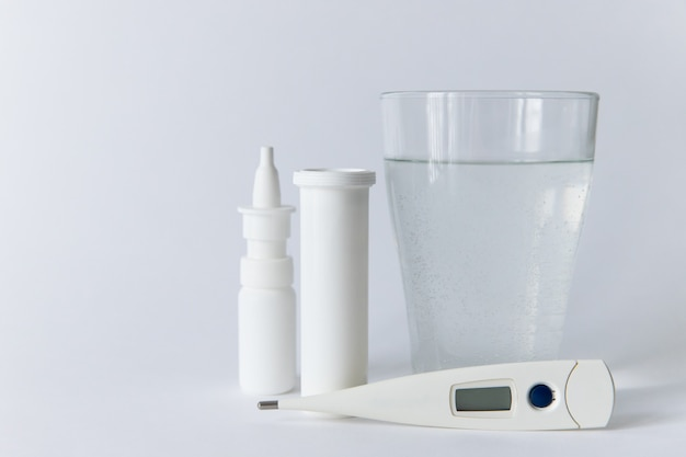 Remédio para spray nasal, frasco de comprimidos branco, termômetro digital médico, vidro