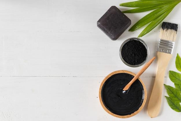 Remédios caseiros para a pele e cuidados faciais, carvão ativado preto e máscara de iogurte, produto cosmético