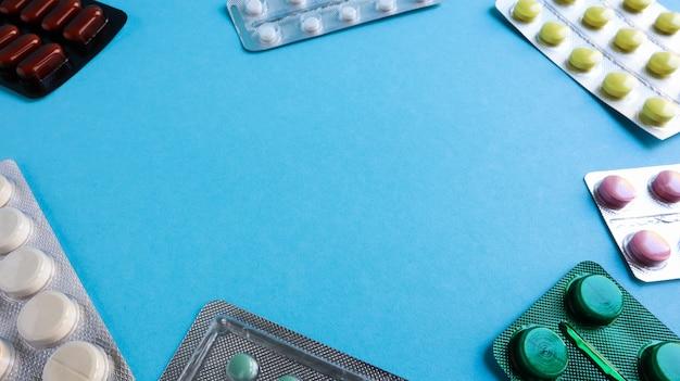 Remédios coloridos e pílulas em embalagens em um fundo azul. copie o espaço. a farmacologia e a medicina lutam pela saúde. tratamento de várias doenças.