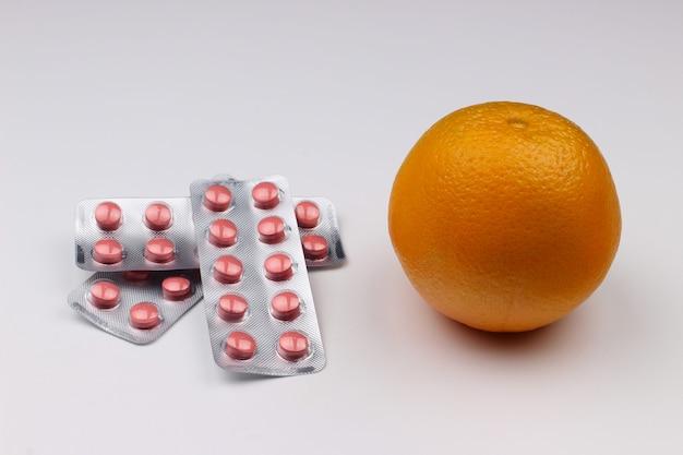 Remédios e laranja em um branco