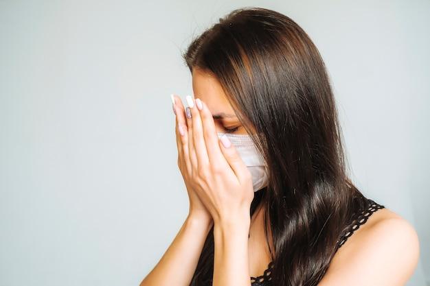 Remédios para coronavírus. dependência de drogas. retrato de uma mulher chorando em uma máscara. triste mulher cobre o rosto com as mãos.