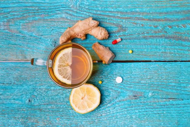 Remédios para resfriados, chá, limão e gengibre no azul de madeira