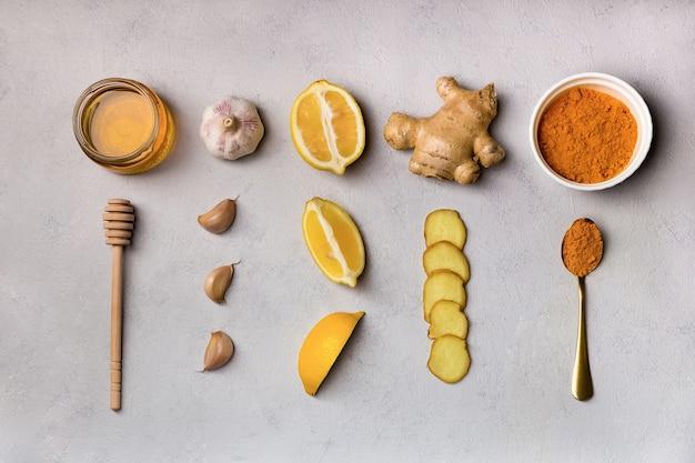 Remédios populares com gengibre, alho, cúrcuma, mel, limão, ingredientes para fazer bebidas, vista de cima.