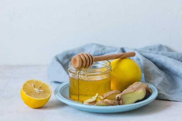 Remédios populares para resfriados. remédio orgânico para resfriado. mel em uma jarra de vidro, limões de gengibre. remédios naturais para resfriados. o mel flui pelo frasco. copie o espaço