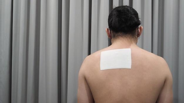 Remendo de alívio da dor ou gesso nas costas do japão do homem.