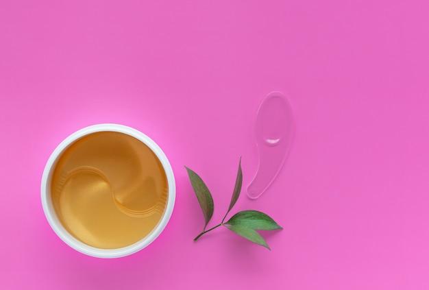 Remendos hidratando dourados para os olhos em um fundo cor-de-rosa. hidratante da pele.