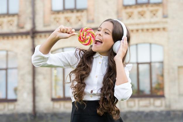 Remix doce. criança feliz cantando microfone doce doce. infância feliz. fones de ouvido de criança criança segurando pirulito. criança feliz com doces ao ar livre se divertindo. calorias e energia. a colegial merece sobremesa.