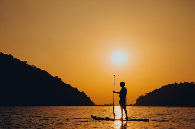 Remo em pé, silhueta de um homem na praia ao pôr do sol