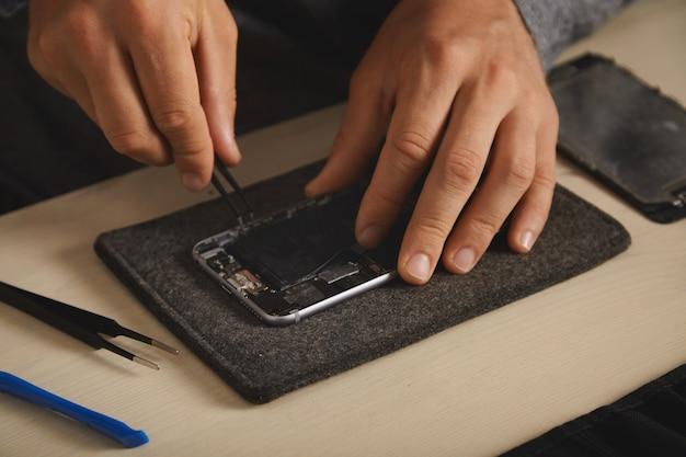 Remoção da bateria bli-on antiga do smartphone desmontado para substituí-la por uma nova, serviço de conserto eletrônico