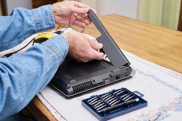 Remoção da bateria do laptop para reparo. chaves de fenda