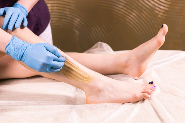 Remoção de cabelo em loja de luxo de spa. pernas de mulheres depiladas com açúcar. açúcar quente.