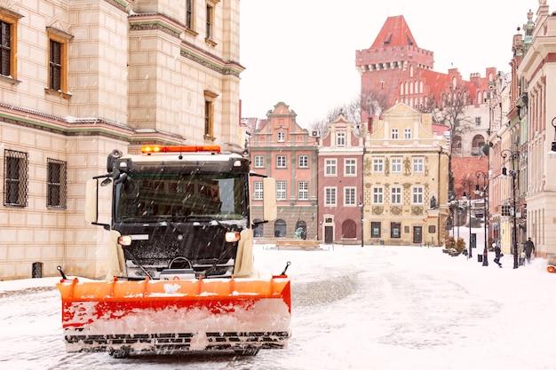 Remoção de neve e limpeza de ruas em poznan. castelo real e praça do mercado velho na cidade velha em dia de inverno nevado, poznan, polônia