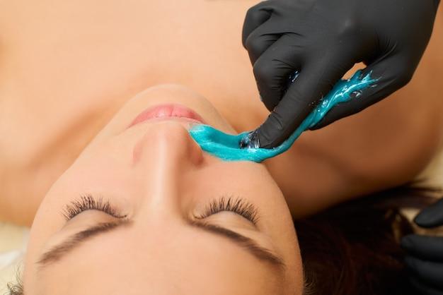 Remoção de pêlos de açúcar do corpo da mulher. procedimento de spa de depilação com cera. mulher esteticista de procedimento. bigode