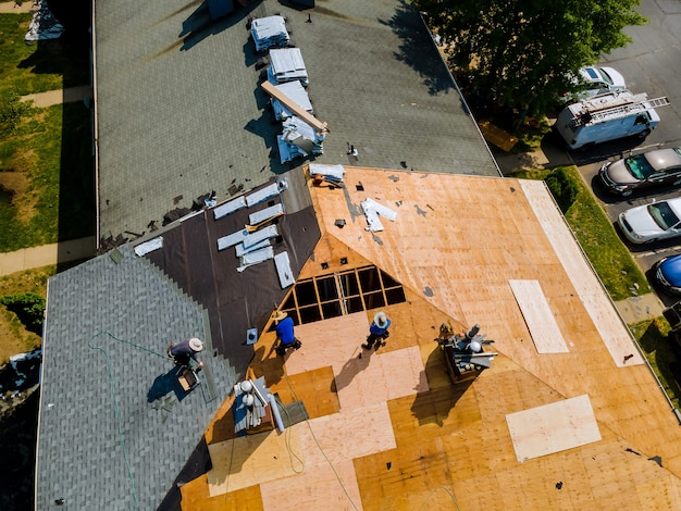 Remoção do telhado antigo e telhados de substituição com novas telhas sendo aplicadas na construção do telhado residencial
