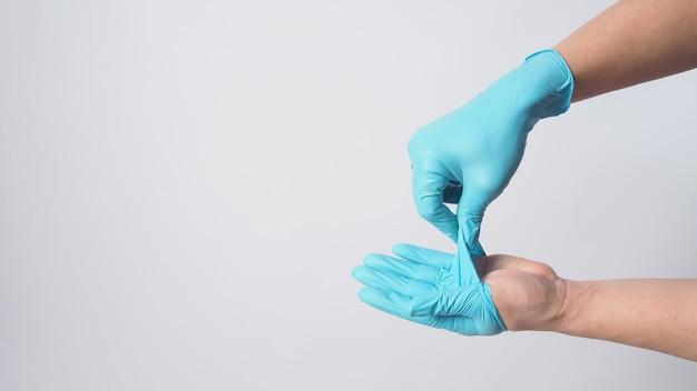 Remova as luvas cirúrgicas azuis removendo a luva de seu corpo no fundo branco.