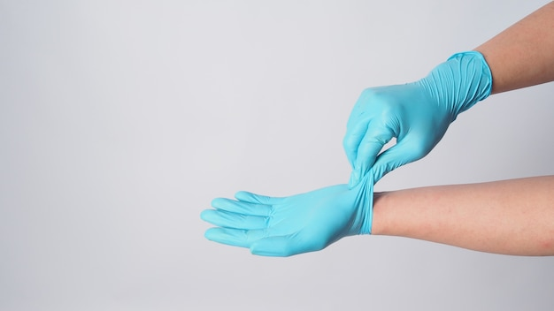 Remova as luvas cirúrgicas azuis segurando a parte externa de uma luva no fundo branco.