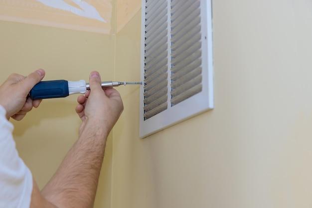 Removendo a tampa do respiradouro na parede com uma chave de fenda quadrada