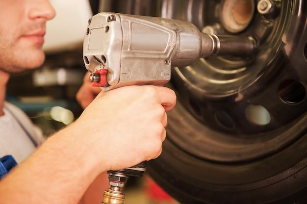 Removendo pneus do carro. close de jovem usando uma chave pneumática enquanto trabalhava com o pneu do carro na oficina