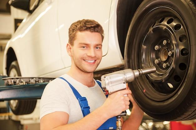Removendo pneus do carro. jovem confiante de uniforme usando uma chave pneumática enquanto trabalha com o pneu do carro na oficina