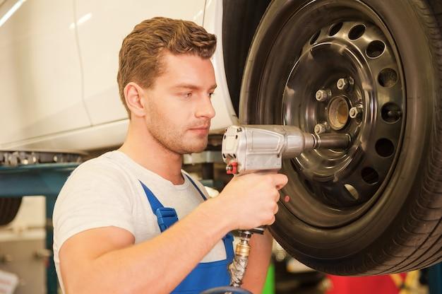 Removendo pneus. jovem confiante de uniforme usando uma chave pneumática enquanto trabalha com o pneu do carro na oficina