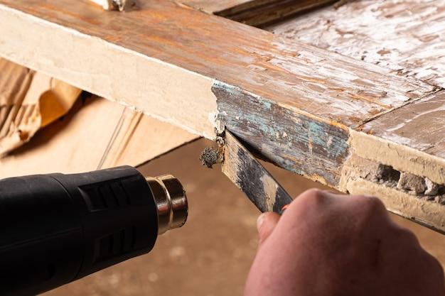 Removendo tinta velha de portas de madeira antigas com uma espátula e uma pistola de calor restaurando superfícies de madeira antigas