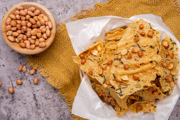 Rempeyek ou peyek kacang é um biscoito indonésio javanês saboroso e frito feito de farinha de arroz