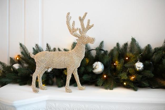 Rena de decoração de natal na lareira branca com galho de árvore de natal ao lado.