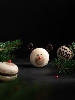 Rena de nariz vermelho de macaron e macaron com número 2020 com ramificações de árvore do abeto em fundo preto escuro. cartão de natal e ano novo