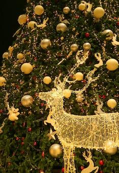 Rena de ouro led iluminada com uma grande árvore de natal