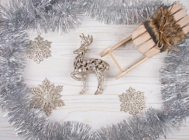 Rena, trenó de natal, enfeites de prata e flocos de neve