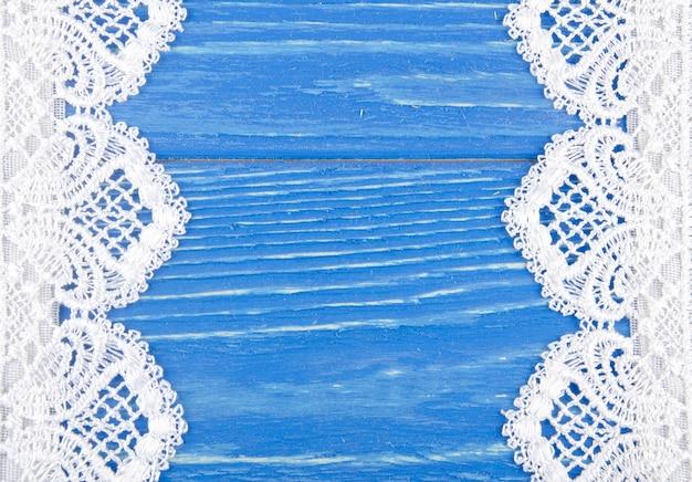 Renda branca sobre um fundo de madeira azul desgastado, formando um quadro