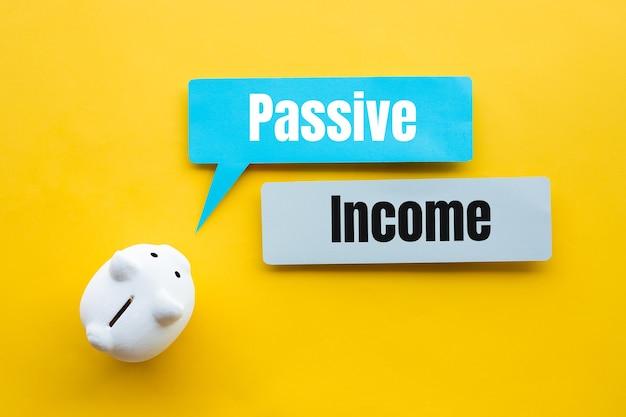 Renda passiva e conceitos financeiros de investimento com texto e cofrinho