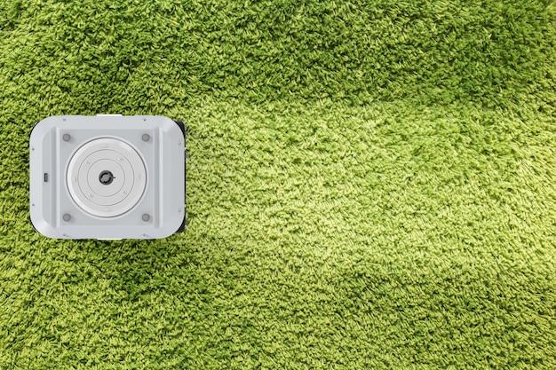 Renderização 3d aspirador de pó robótico na vista superior do tapete verde