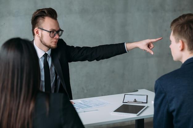Renegar o acordo. relacionamento profissional fracassado. homem de negócios jovem quebrando acordo, mostrando a porta aos parceiros.