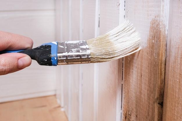 Renovação da casa de madeira, repintura manual de uma parede de tábuas para a cor branca com pincel e tinta látex ou anrílica de interior, materiais ecológicos e respiráveis.