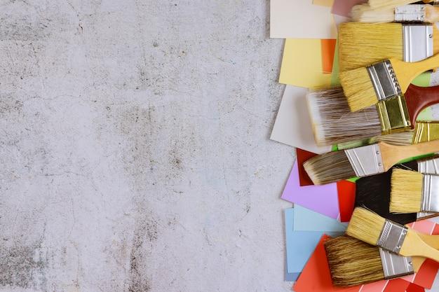 Renovação da mesa de trabalho que decora ferramentas de pincel de pintura e paleta de cores com vista para o espaço da cópia