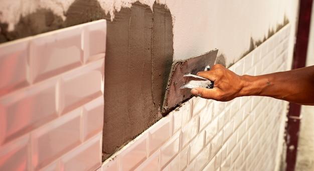 Renovação de casa, colocação de telhas de cerâmica na parede.