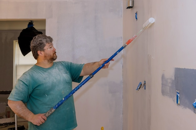 Renovação do interior, parede masculina pintada à mão com apartamento de pintura a rolo de pintura, reformando