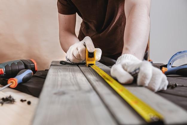 Reparação, construção e conceito de casa - close-up das mãos masculinas, medindo as placas de madeira. o carpinteiro profissional faz medições precisas com uma fita métrica amarela e um lápis. ferramentas de marcenaria.