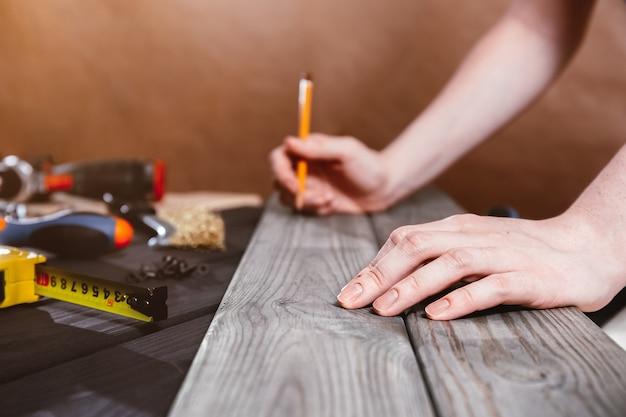 Reparação, construção e conceito de casa - close-up de mãos femininas, medindo placas de madeira. o carpinteiro profissional faz medições precisas com uma fita métrica amarela e um lápis. ferramentas de marcenaria
