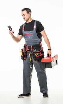 Reparação, construção e construção. trabalhador masculino ou construtor com smartphone e ferramentas de trabalho no cinto e caixa