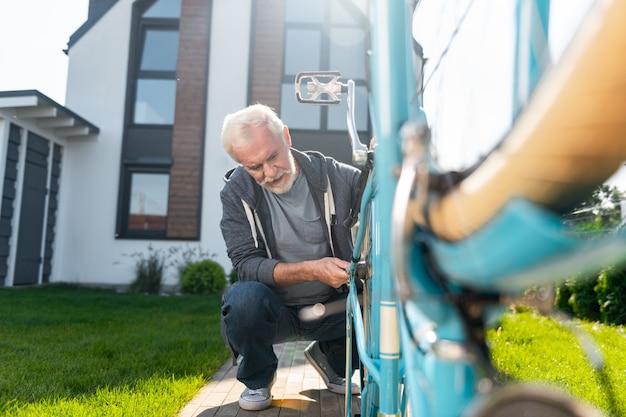 Reparação de homem. homem barbudo de cabelos grisalhos consertando bicicleta velha azul perto de sua casa particular em um dia quente