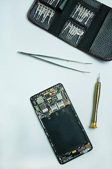 Reparação de smartphone. smartphone desmontado, chaves de fenda para desmontar o telefone. vista plana leiga, superior.