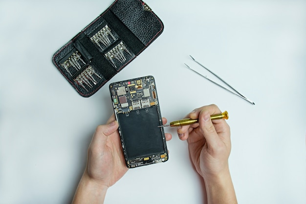 Reparação de smartphone. smartphone desmontado nas mãos masculinas. kit de reparação de smartphone. vista plana leiga, superior. espaço para texto.