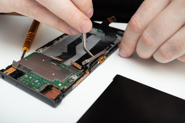 Reparação de telemóveis. o assistente coleta um smartphone dos detalhes