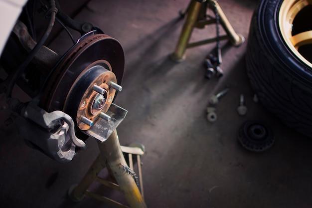 Reparação do sistema de travões de disco no suporte de macaco nas oficinas de reparação automóvel.